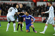 Cesc Fabregas of Chelsea is helped to his feet by Bafetimbi Gomis of Swansea city after being fouled. . Barclays Premier League match, Swansea city v Chelsea at the Liberty Stadium in Swansea, South Wales on Saturday 17th Jan 2015.<br /> pic by Andrew Orchard, Andrew Orchard sports photography.