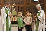 Na hun beëdiging nemen de pastoors Bernd Wallet en Annemieke Duurkoop een presentje aan van de kinderen uit de parochie. Op zondag 31 oktober is in de Getrudiskathedraal in Utrecht  Annemieke Duurkoop als eerste vrouwelijke plebaan van Nederland geïnstalleerd. Duurkoop wordt de nieuwe pastoor van de Utrechtse parochie van de Oud-Katholieke Kerk (OKK), deze kerk heeft geen band met het Vaticaan. Een plebaan is een pastoor van een kathedrale kerk, die eindverantwoordelijk is voor een parochie. Eerder waren bij de OKK al twee vrouwelijk priesters geïnstalleerd, maar die zijn geen plebaan.<br /> <br /> After being installed as pastor Bernd Wallet (left) and Annemieke Duurkoop (right) are receiving presents from children. At the St Getrudiscathedral in Utrecht the first female dean of the Old-Catholic Church (OKK), Annemieke Duurkoop, is installed together with a new pastor Bernd Wallet. The church has no connections with the Vatican.