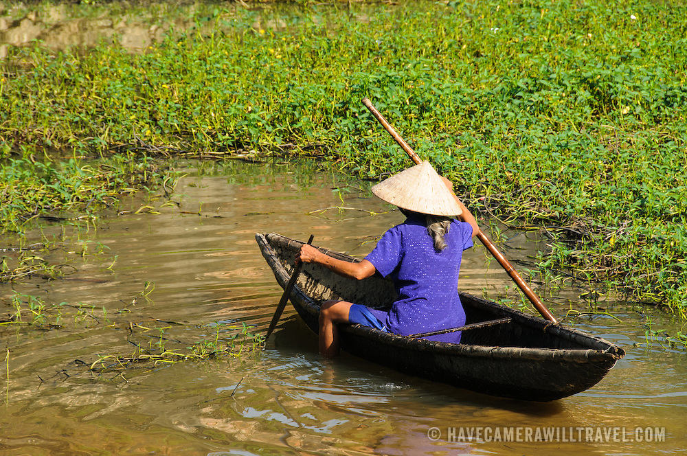 A woman in a wooden canoe navigates the muddy shallows next to some reeds in Hue, Vietnam.