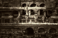 """""""The glow of the Holy Cross in the ruins of the Colosseum - BW""""…<br /> <br /> The Colosseum is one of Rome's most popular tourist attractions and still has close connections with the Roman Catholic Church, as each Good Friday the Pope leads a torch lit """"Way of the Cross"""" procession that starts in the area around the Colosseum.  The Colosseum is generally regarded by Christians as a site of the martyrdom of large numbers of believers during the persecution of Christians in the Roman Empire, as evidenced by Church history and tradition.  A Cross stands exultant in the Colosseum center with a plaque, stating:  """"The amphitheatre, one consecrated to triumphs, entertainments, and the impious worship of pagan gods, is now dedicated to the sufferings of the martyrs purified from impious superstitions.""""  In viewing many historical sites during my journey in Italy, seeing the iconic Colosseum for the first time…I became awestruck.  It is as grand in person as it appears in the media, and it seems to hold a very mystical aura.  Climbing the ancient steps inside, one cannot help but feel not only the suffering of its past, but the forgiveness and sacrifice of its present stature."""