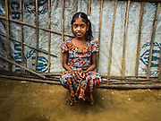07 NOVEMBER 2014 - SITTWE, RAKHINE, MYANMAR: A Rohingya Muslim girl in front of her tent in an IDP camp for Rohingya near Sittwe. After sectarian violence devastated Rohingya communities and left hundreds of Rohingya dead in 2012, the government of Myanmar forced more than 140,000 Rohingya Muslims who used to live in and around Sittwe, Myanmar, into squalid Internal Displaced Persons camps. The government says the Rohingya are not Burmese citizens, that they are illegal immigrants from Bangladesh. The Bangladesh government says the Rohingya are Burmese and the Rohingya insist that they have lived in Burma for generations. The camps are about 20 minutes from Sittwe but the Rohingya who live in the camps are not allowed to leave without government permission. They are not allowed to work outside the camps, they are not allowed to go to Sittwe to use the hospital, go to school or do business. The camps have no electricity. Water is delivered through community wells. There are small schools funded by NOGs in the camps and a few private clinics but medical care is costly and not reliable.   PHOTO BY JACK KURTZ