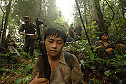 A young boy stands guard in the jungle while his group rests, near Vang Vieng, Laos, June 30, 2006...**EXCLUSIVE, no tabloids without permission**  .Pictured are a group of Hmong people who report an attack against them April 6, 2006 by Lao and Vietnamese military forces.  26 people perished, 5 were injured, and 5 babies died shortly after because their dead mothers could not breast-feed them.  Only one adult male was killed, the other 25 victims were women and children (17 children).  The Lao Spokesman for the Ministry of Foreign Affairs says this is a fabrication, an investigation has been completed, and there was no attack.  The Hmong group says no officials have interviewed witnesses or visited the crime scene, a point the Lao Spokesman did not deny.  ..The Hmong people pictured have hidden in remote mountains of Laos for more than 30 years, afraid to come out.  At least 12,000 are said to exist, with little food, scavenging in the jungle. Most have not seen the modern world.  The CIA trained and funded many Hmong hill tribes in Laos from 1961 to 1973 to fight communism.  The Hmong suffered massive casualties defending their homeland and rescuing US pilots.  When America withdrew from the conflict most Hmong were left alone to face the might of the North Vietnamese Army.  The Royal Lao Government fell to the communists and the Hmong became outcasts in the country they fought to defend.  Since 1975, under the communists, thousands of reports evidence the Hmong have suffered frequent persecution, torture, mass executions, imprisonment, and possible chemical weapons attacks.  Reports of these atrocities continue to this day.  The Lao Government generally denies the jungle people exist or that any of this is happening.  The Hmong group leader, Blia Shoua Her, says they are not part of the Hmong resistance and want peace.  He claims they are just civilians defending their families, hoping to surrender to the UN....