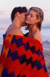 couple wrapped in a blanket on the beach