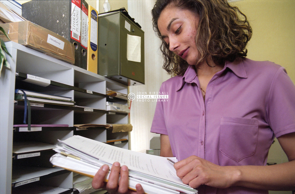 Young woman reading document in school office,