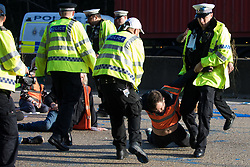 Ockham, UK. 21st September, 2021. Surrey Police officers drag an Insulate Britain climate activist from the clockwise carriageway of the M25 between Junctions 9 and 10. Activists briefly halted traffic on both carriageways of the motorway as part of a campaign intended to push the UK government to make significant legislative change to start lowering emissions.