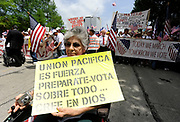 """Maria Teresa Ocampo from Garland Texas carries a sign the reads """"Peaceful unity is strength. Prepare yourself, vote and above all believe in God """"during the MegaMarch for Immigration Reform,  May 01, 2010"""