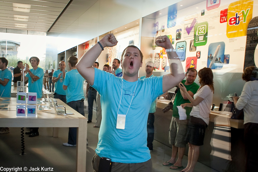 12 JUNE 2009 -- SCOTTSDALE, AZ: An employee of the new Apple Store in Scottsdale cheers before the store's grand opening Friday. The outlet will be Arizona's largest Apple Store, occupying nearly 10,000 square feet in the Outdoor Lifestyle Center in the Scottsdale Quarter. The store, the fifth in the Phoenix area, uses a radically different design from other Apple Stores in some respects. Ceilings in the building are approximately 20 feet high, and lined with a 75-foot long skylight, reducing dependence on artificial lighting. Aiding the skylight is an all-glass front and rear, permitting visitors to see directly through the store. More than one thousand people lined to get into the store during the grand opening. Photo by Jack Kurtz