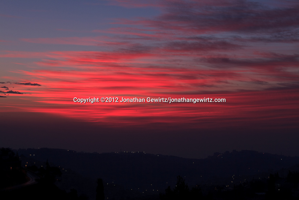 Red pre-dawn sky over the Mountains of Moab behind the village of Abu Dis on the eastern outskirts of Jerusalem. WATERMARKS WILL NOT APPEAR ON PRINTS OR LICENSED IMAGES.