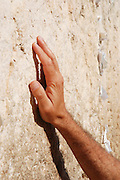 Israel, Jerusalem Old City, close up of a male hand touches the Wailing wall