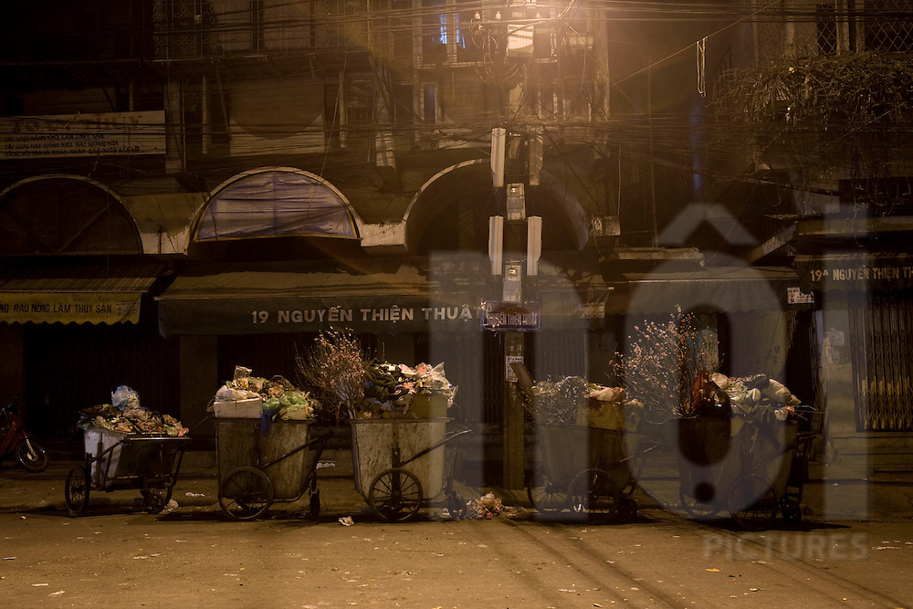 Garbage dumpsters, fully loaded with rubbish, are lined up in an empty street of Hanoi at night,  Vietnam, Southeast Asia