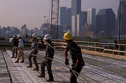Stock photo of a line of men working with rebar on the roof of a new building near downtown Houston Texas