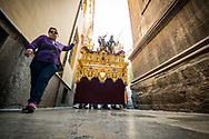 A woman takes a video of an ongoing float during one of the processions of the Holy Week in a tiny alley of Granada. Andalusia. Spain