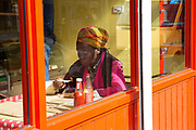 A lady wearing a brightly coloured headscarf eats lunch at a colourful Caribbean restaurant on 7th June 2017 in Brixton, London, United Kingdom. A sunny day on Atlantic Road in Brixton, South London.