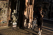 Cyclist courier pushes bike on pavement with a small girl statue credited to the 19th century Florence-born  Raffaello Romanelli