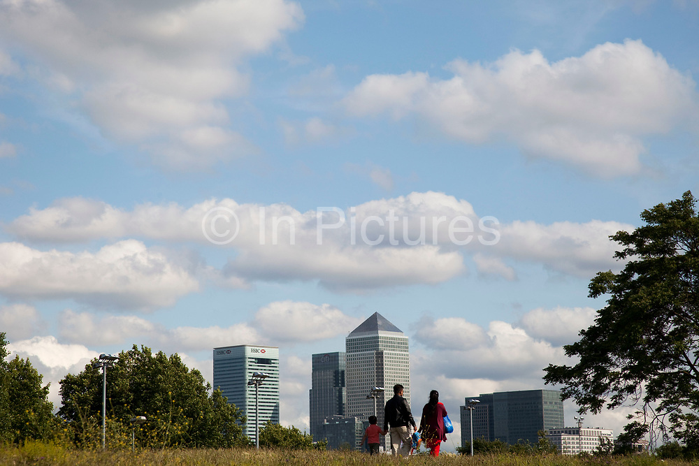 Family walk past the skyline of Canary Wharf in East London. Canary Wharf is a major business district located in London, United Kingdom. It is one of London's two main financial centres, and contains many of the UK's tallest buildings, including the second-tallest, One Canada Square.