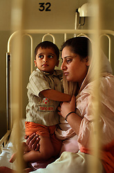 Abdul Wahab, 2, waits with his mother, Amna Bibi, during treatment for a cough inside the Children's Hospital at the Pakistan Institute of Medical Sciences, P.I.M.S., in Islamabad, Pakistan on Sept. 18, 2007.