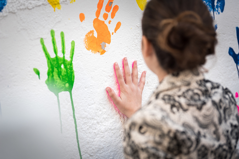 17 February 2020, Zarqa, Jordan: A girl paints her handmark on the wall of the Lutheran World Federation community centre in Zarqa. Through a variety of activities, the Lutheran World Federation community centre in Zarqa serves to offer psychosocial support and strengthen social cohesion between Syrian, Iraqi and other refugees in Jordan and their host communities.