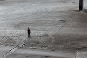 A man stands in an empty lot marked with truck tracks at a coal mine and processing facility in Liulin, Shanxi province, China, on Thursday, May 19, 2016. Shanxi is facing a challenge shared by a sweeping region across Chinas industrial north: how to shut down cash-burning mines that employ millions of people whose prospects are uncertain in the new economy promised by President Xi Jinping.