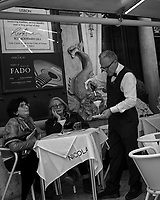 Waiter flaming dessert. Afternoon walkabout in Lisbon. Image taken with a Leica CL camera and 23 mm f/2 lens.