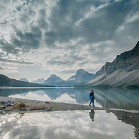 A hiker walks beside Bow Lake in Banff National Park.  Behind are (L to R)  Mount Andromache, Mount Hector, Bow Peak, Bow Crow Peak and Crowfoot Mountain.