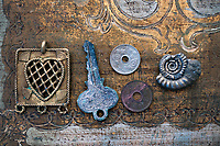 Still Life Photography of symbolic things: a heart, old key, two chinese coins, and a spiral nautilus fossil ammonite. Symbolic objects: relationship, romance, marriage, dreams, travel, or eternity.