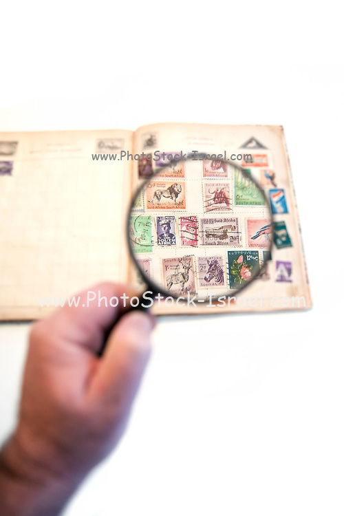 Stamp collecting hobby. Collector uses a magnifying glass to view his South African stamps from the 60's