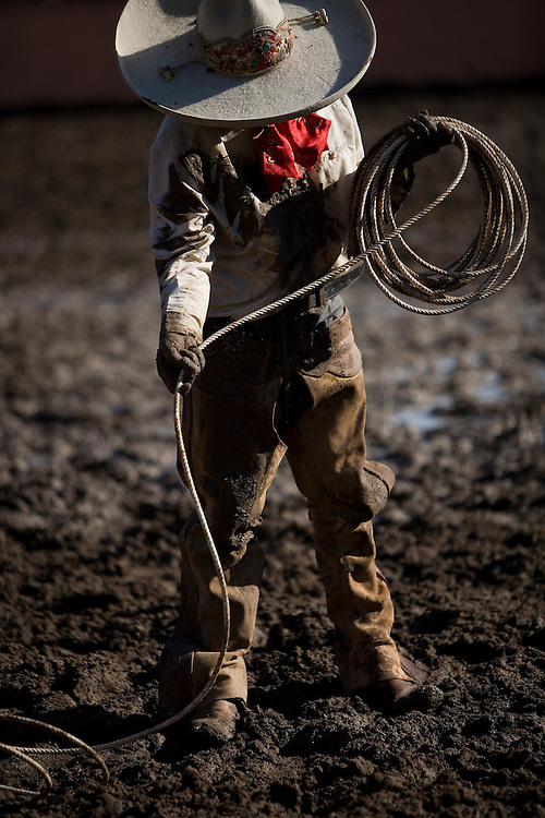 Photo by Julia Robinson.A charro recoils his reata after being dragged through the mud by a wild horse.  For all the pageantry of the charro suit, or traje, it protects the competitor from rope burns and head injuries.