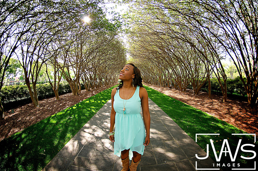 Young lady standing on the sidewalk under the arching trees of the Dallas Arboretum during the Spring time in April.