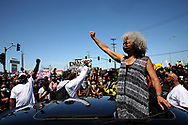 Activist, professor, and author Dr. Angela Davis pumps her fist during a Juneteenth shut down at the Port of Oakland, Friday, June 19, 2020, in Oakland, Calif. Cranes and berths came to a standstill as longshoremen in ports throughout California stopped work Friday, joining thousands of Californians who marched, rallied and drove in car caravans to commemorate Juneteenth and demand racial equality. Juneteenth marks the day in 1865 when federal troops arrived in Galveston, Texas, to take control of the state and ensure all enslaved people be freed, more than two years after the Emancipation Proclamation.