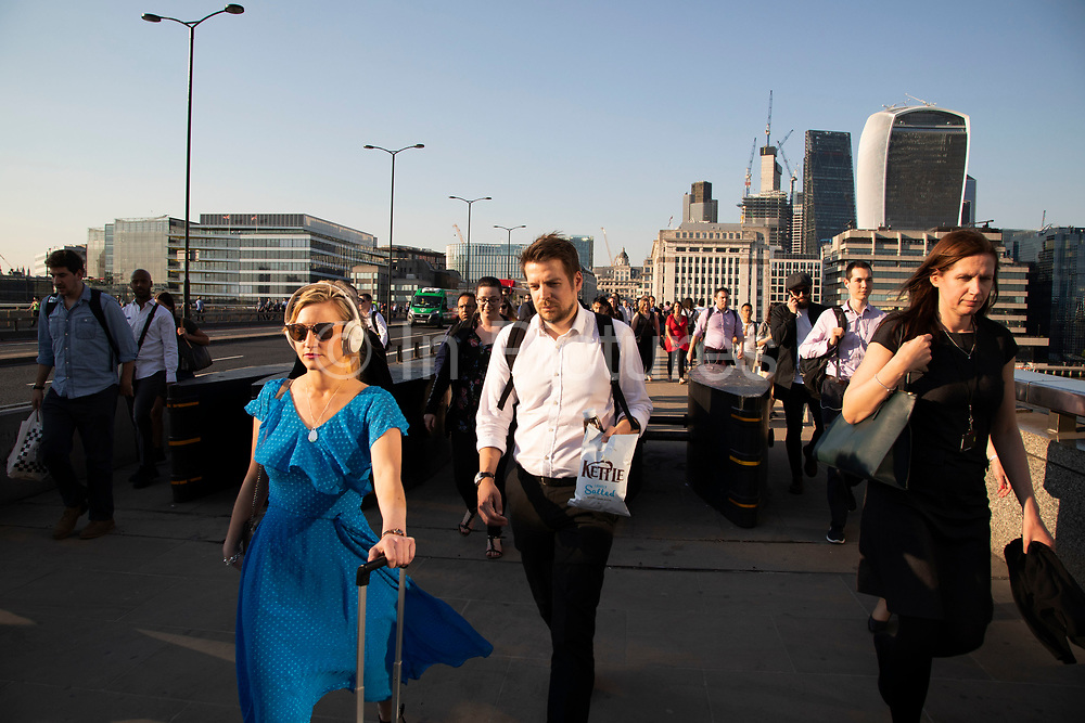Commuters crossing south on London Bridge at rush hour at the end of the working day in the financial district of the City of London, England, United Kingdom.
