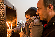 A young boy and his father light candles during the Sunday service at the Samatya Kilisesi in Fatih, Istanbu, Turkey.