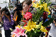 14 SEPTEMBER 2003 - CANCUN, QUINTANA ROO, MEXICO:  The daughter of Lee Kyung-hae carries flowers to an alter for her father during a memorial service Sunday for her father, a Korean farm activist who publicly committed suicide Wednesday in Cancun to protest World Trade Organization agricultural policies, has been built where he died in a park in Cancun. Thousands of protestors opposed to the World Trade Organization and globalization have come to Cancun to protest the WTO meetings taking place in the hotel zone. Mexican police restricted most of the anti-globalization protestors to downtown Cancun, about five miles from the convention center.  PHOTO BY JACK KURTZ