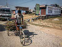 Man riding his bicycle laden with sticks on the road to Nepalgunj.