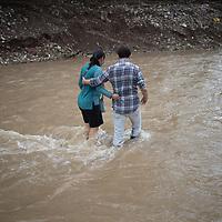 Rony Turcios and Xiomara de Turcios hold each other as they cross Quebrada El Calan near San Pedro Sula, Honduras. The bridge was washed away in the floods of hurricanes Eta and Iota.