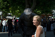 A tourist has an encounter with statue mime artist who starts to move as she approaches, making her laugh. On this part of the Southbank in London, UK there are a lot of these living statues. The South Bank is a significant arts and entertainment district, and home to an endless list of activities for Londoners, visitors and tourists alike.