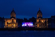 Royal Naval College, Greenwich, photographed at night from Island Gardens, across the Thames. The Queen's House is lit with pink and purple. London, England.