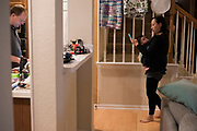 AUSTIN, TEXAS - FEBRUARY 9: Jinny Suh checks her phone with her 4-month-old son at her home in Austin, Texas on February 9, 2017. Jinny is a pro-vaccine advocate in addition to running her own businesses from home and raising her two sons. (Photo by Cooper Neill for The Washington Post)