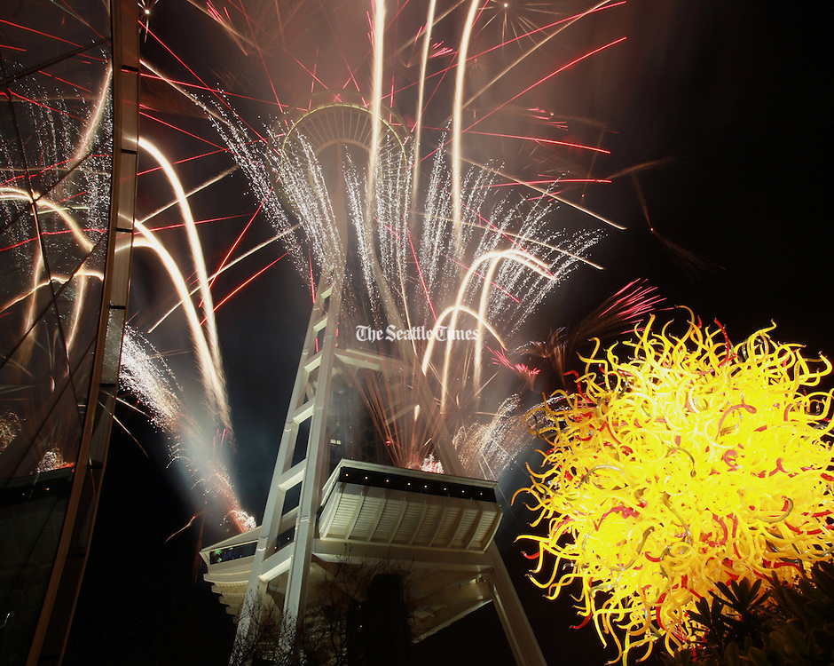 """Fireworks shoot from the Space Needle in Seattle at midnight on New Year's Eve, 2012, ringing in the new year. In the foreground at right is """"Pacific Sun,"""" a work on the grounds of Chihuly Garden and Glass. (Ken Lambert / The Seattle Times)"""