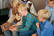 "Aug 10, 2008 -- COLORADO CITY: Boys in the Jessop family share a hymnal before a prayer service in the living room of their home in Colorado City, AZ. The Jessops are polygamists and members of the FLDS. Colorado City and neighboring town of Hildale, UT, are home to the Fundamentalist Church of Jesus Christ of Latter Day Saints (FLDS) which split from the mainstream Church of Jesus Christ of Latter Day Saints (Mormons) after the Mormons banned plural marriage (polygamy) in 1890 so that Utah could gain statehood into the United States. The FLDS Prophet (leader), Warren Jeffs, has been convicted in Utah of ""rape as an accomplice"" for arranging the marriage of teenage girl to her cousin and is currently on trial for similar, those less serious, charges in Arizona. After Texas child protection authorities raided the Yearning for Zion Ranch, (the FLDS compound in Eldorado, TX) many members of the FLDS community in Colorado City/Hildale fear either Arizona or Utah authorities could raid their homes in the same way. Older members of the community still remember the Short Creek Raid of 1953 when Arizona authorities using National Guard troops, raided the community, arresting the men and placing women and children in ""protective"" custody. After two years in foster care, the women and children returned to their homes. After the raid, the FLDS Church eliminated any connection to the ""Short Creek raid"" by renaming their town Colorado City in Arizona and Hildale in Utah.     Photo by Jack Kurtz / ZUMA Press"