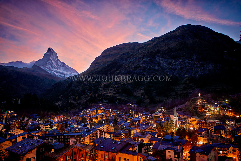 The sun sets on the town of Zermatt with the Matterhorn mountain in the background.