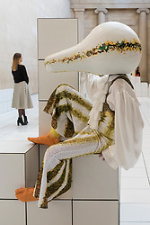"""© Licensed to London News Pictures. 21/03/2018. LONDON, UK. A performer wears a squash-like costume at the preview of """"The Squash"""", an immersive installation combining performance and sculpture by 2016 Turner Prize nominee Anthea Hamilton.  At Tate Britain, performers will wear outfits from a collection of seven elaborate squash-like costumes to showcase Hamilton's work amidst 7,000 white floor tiles spanning the entire Duveen Galleries and Tate Britain's own sculpture collection.  The show runs 22 March to 7 October 2018.  Photo credit: Stephen Chung/LNP"""
