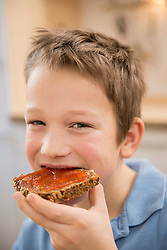 Portrait of smiling boy eating bread with jam