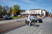 In Zeist rijdt een vrouw met een kind achterop door het centrum terwijl een auto haar inhaalt.<br /> <br /> Cyclists in the city center of Zeist.