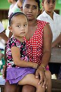 A girl sits on her mother's lap as they wait during a vaccination session at the primary school in the town of Coyolito, Honduras on Wednesday April 24, 2013.