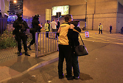 Armed police (left) at Manchester Arena after reports of an explosion at the venue during an Ariana Grande gig.