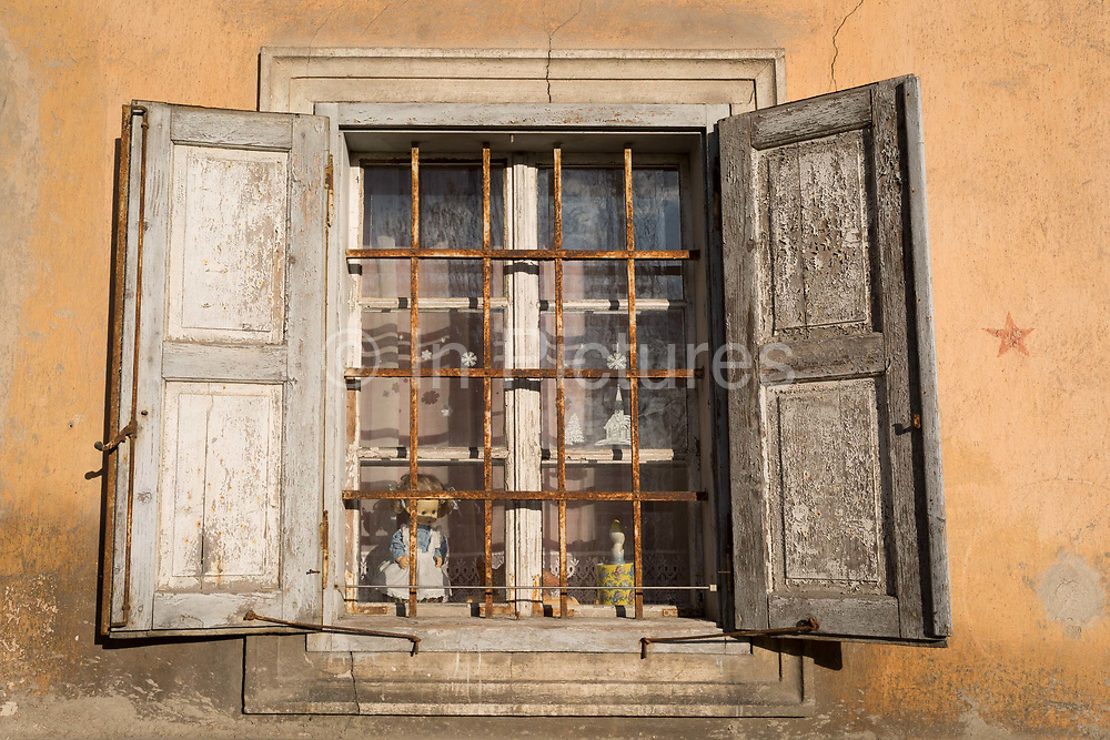 Old windows with a childs doll inside, of a Slovenian village house on 18th June 2018, in Bohinjska Bela, Bled, Slovenia.
