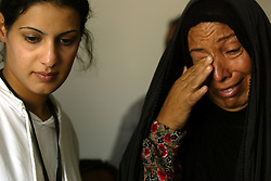 Alyaa Abdul Hassan Abbood, 23, a translator, tries to comfort Beheyen Ibrahim Jar, who just found out that her husband died at the hands of a U.S. soldier, Baghdad, Iraq, Sept. 27, 2003. Abbood works with the U.S. military to mediate as Iraqi civilians come to receive monetary compensation for damages done by American troops in Baghdad.