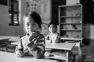 Portrait of two young vietnamese girls in their classroom. North Vietnam, Asia