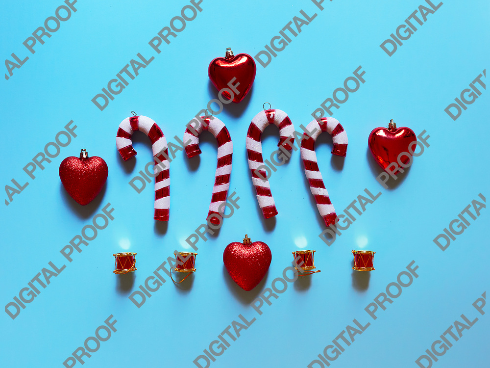 Christmas candy cane drums hearts and gifts at studio above view over a light blue background isolated flatlay