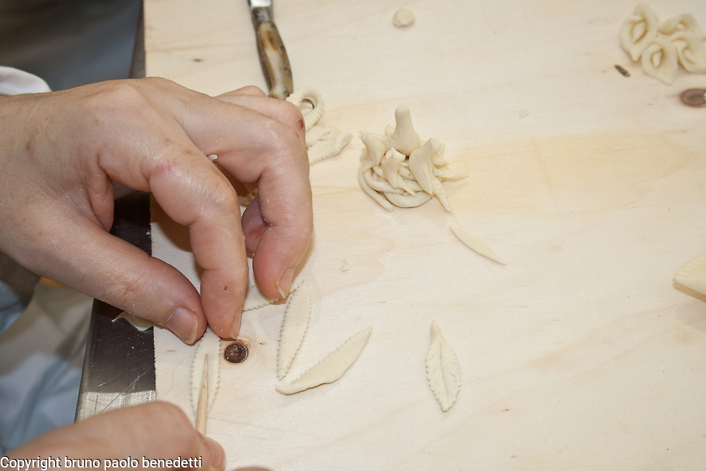 carving bread leaves for bread decoration using a stick on wood counter with other bread decorations, Sardinian bread sculpture, the Pani Pintau